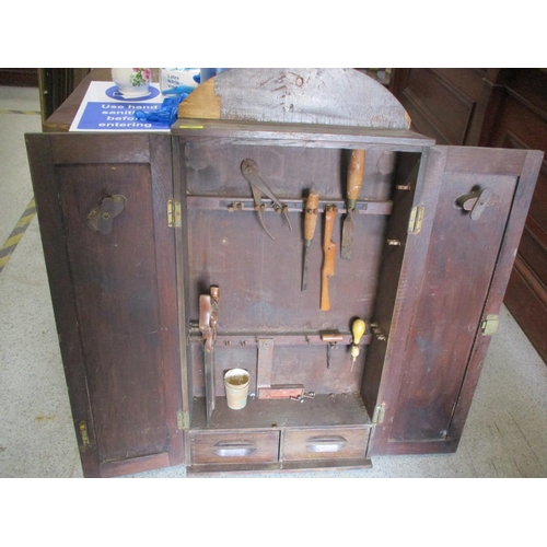 50 - A 1930s oak finished, twin door, wall mounted tool cabinet, containing a small assortment of tools L...