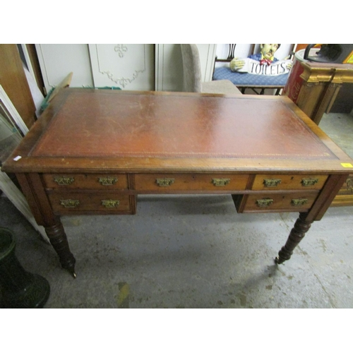 85 - A late Victorian/Edwardian walnut desk, faded red leather inset scriber over five short drawers with...