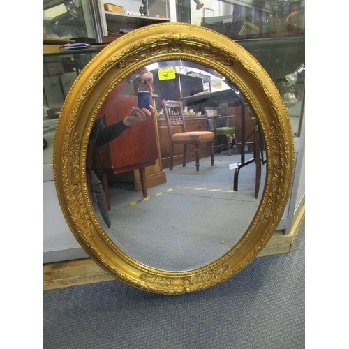 90 - A contemporary oval gilt framed wall mirror with bevelled glass plate 28 1/2