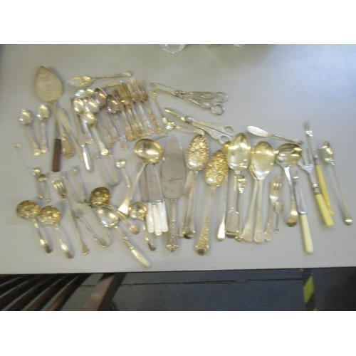 92 - A mixed lot of silver plated flatware to include two grape scissors, berry spoons and other items Lo...