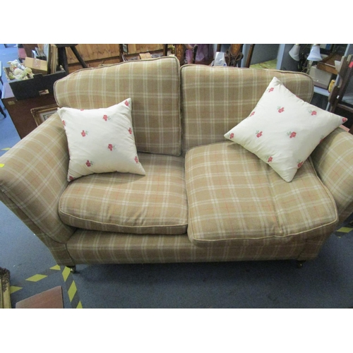 93 - A modern two-seater sofa upholstered in a chequered pattern with  loose cushions, on turned front le...