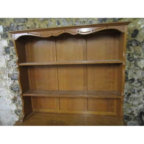 106 - A light oak carved dresser, the top with two plate shelves above a base with two short drawers and t...