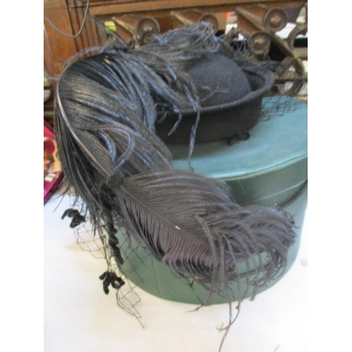 359 - A Herald & Heart Hatters of London ladies black felt hat with additional black feather and veil, tog...
