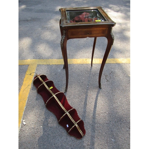 392 - Mahogany and inlaid brass display table with glazed top, applied brass plaques to the legs, and a gi...