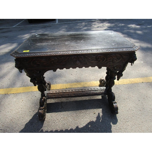396 - A Victorian carved oak table with single frieze drawer flanked by lion head masks with brass ring ha...