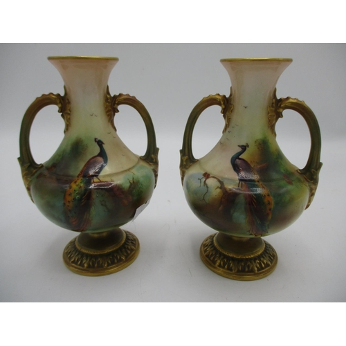 135 - A pair of small early 20th century Royal Worcester vases of bulbous form with twin handles, on a spl...