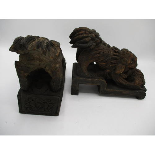 35 - A pair of 20th century Chinese carved wooden foo dogs with a ball, on a stepped base, 7