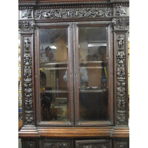 221 - A late 19th century Edwards & Roberts Italianate walnut breakfront bookcase cabinet carved with figu...