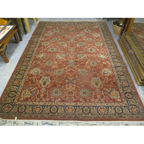 47 - A machine woven red ground rug having a flora design and multiguard borders, 118