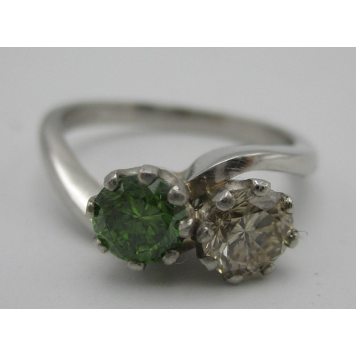 212 - A platinum two stone diamond ring, the green diamond 0.69ct and a round cut diamond colour E-F, VSI-...