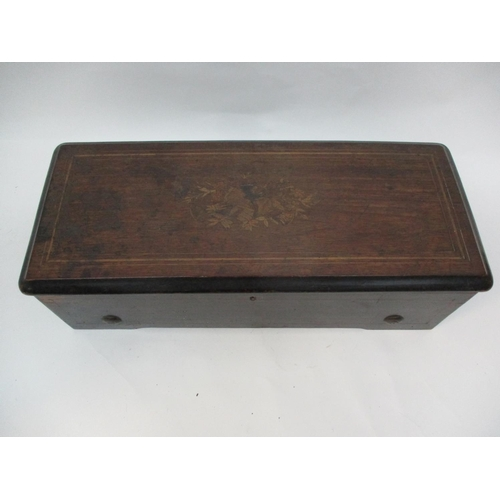 216 - A late 19th century inlaid walnut and marquetry cased musical box, the lid decorated with musical in...