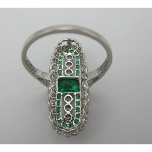 246 - A platinum elongated ring set with a central emerald flanked by six diamonds with a band of emeralds...