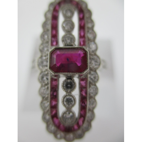 247 - A platinum elongated ring set with a central ruby flanked by six diamonds within bands of diamonds a...
