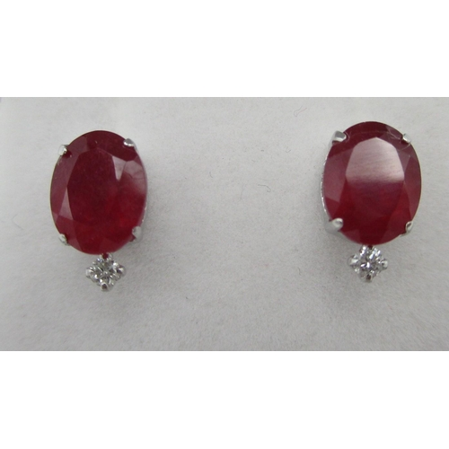 260 - A pair of platinum stud earrings, each set with a treated ruby and a diamond below, rubies 4ct total...