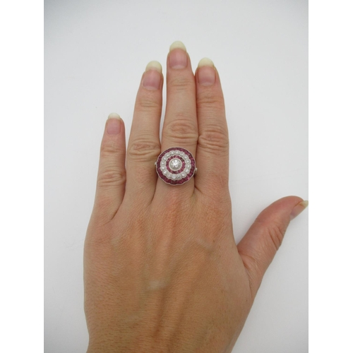 262 - A platinum flower design ring set with bands of diamonds and calibre cut rubies Location: CAB