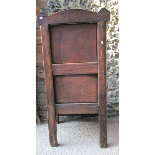 269 - An 18th/19th century oak Wainscot chair with an arched carved crest, panelled back, level arms and p...