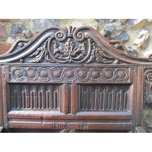 270 - A 17th/18th century oak Wainscot chair with a carved crest, panelled back, scrolled arms and planked...