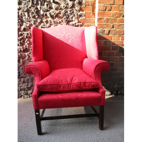 271 - A George III wing back armchair upholstered in a red leaf patterned fabric, with a cushioned seat, o...