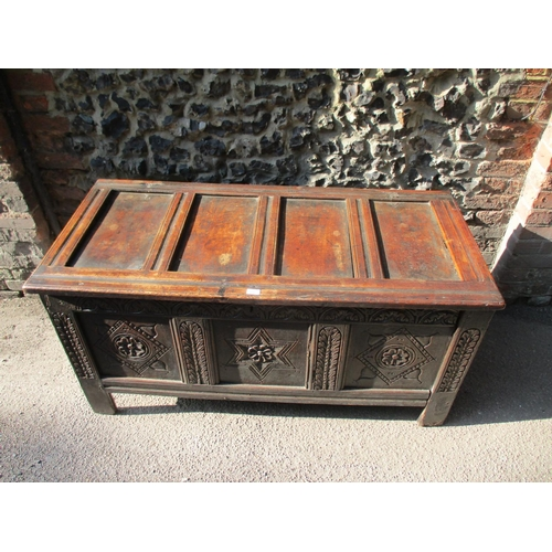 272 - An 18th century oak chest with a hinged panelled top and carved, panelled front, on extended style f...