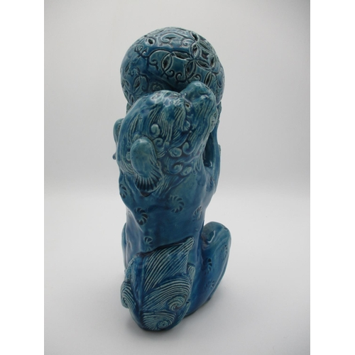 28 - A 20th century Chinese blue glazed Foo dog on its haunches, holding up a ball, 9 1/2