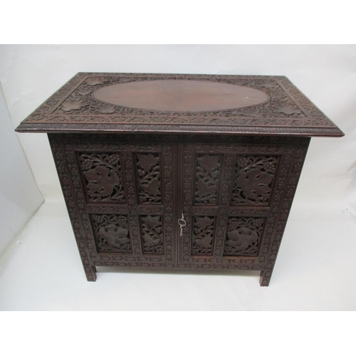 42 - An early 20th century Indian small folding carved hardwood cabinet, decorated with fruiting vines an...