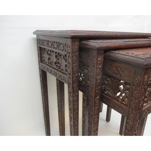 43 - A nesting set of three early 20th century Anglo Indian carved hardwood occasional tables with vine a...
