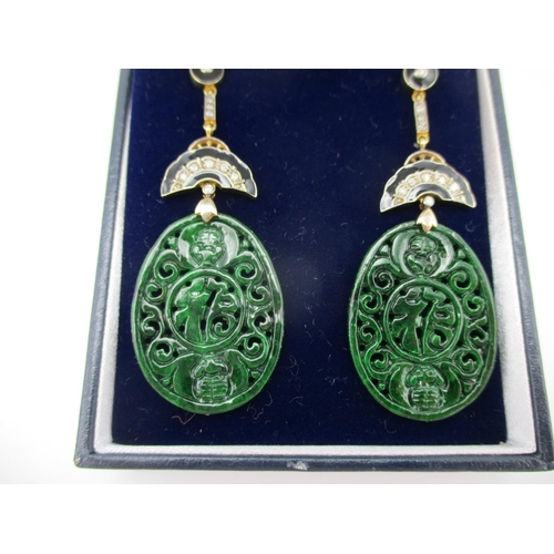 59 - A pair of Asian 9ct gold and silver drop earrings, the carved and pierced jade panels decorated with...