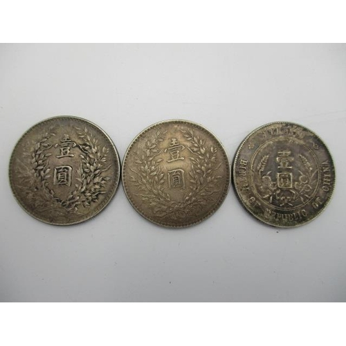 133 - Four coins comprising of a Birth of Republic of China memento, silver dollars, a middle eastern coin...