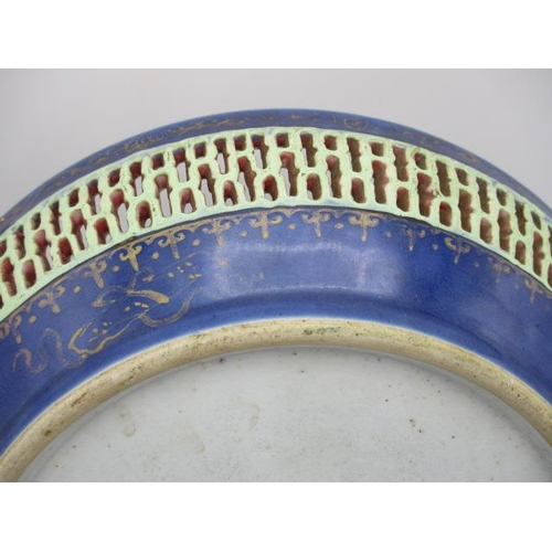 20 - A large 18th century Chinese dish with a pierced band, designed with a powder blue rim with gilt emb...