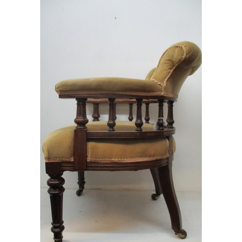 244 - An early 20th century mahogany library chair with a button upholstered crest, level arms and turned,...