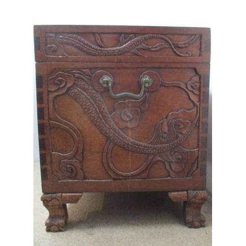 46 - An early 20th century Chinese hardwood chest, the top, front and sides carved with dragons and cloud...