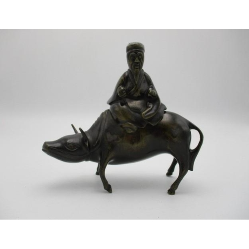 48 - A 19th century Chinese bronze incense burner, fashioned as a Tao Philosopher Lazo riding a water buf...
