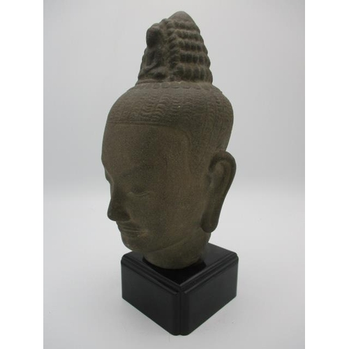 51 - A 19th/20th century Indian/Pakistan carved stone head of a Buddha, with a figure to the  tied up hai...