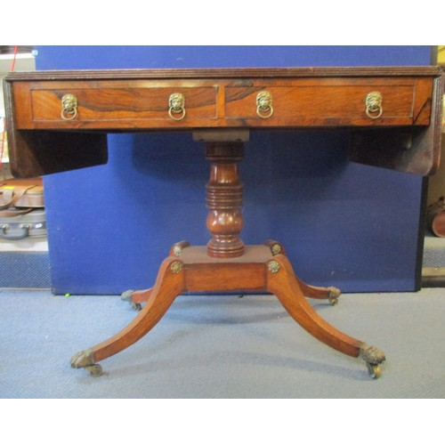 258 - A Regency brass inlaid rosewood sofa table with twin fall flaps and a reeded edge, over a pair of dr...
