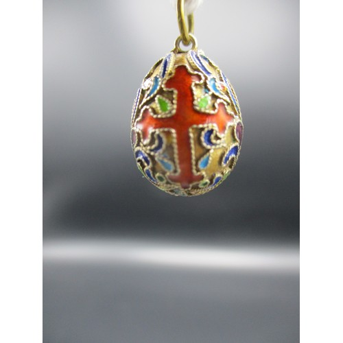 274 - A yellow metal and enamel pendant in the form of an egg decorated with two crosses and scrolls 3/4