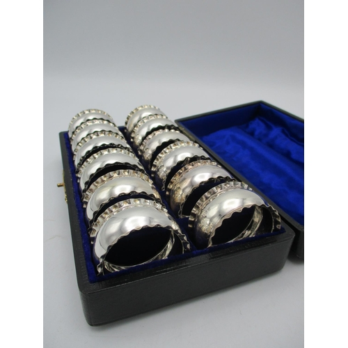 35 - A cased set of twelve Edwardian silver napkin rings by C.T Burrows & Sons, Birmingham 1905, designed...