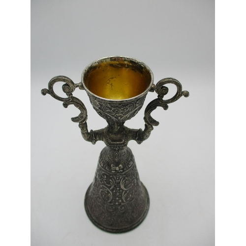 50 - A large Continental silver plated wager cup, cast as a lady holding aloft a swivelling cup, unmarked...