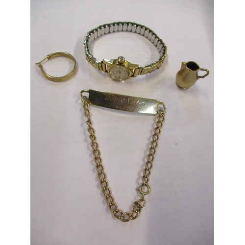 11 - A 9ct gold identity bracelet, a 9ct gold single earring, a gold coloured miniature jug and an 18ct g...