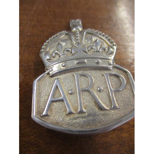 47 - A silver cigarette case, initialled C.C makers mark, 118.9g together with a 1930's silver ARP badge,...