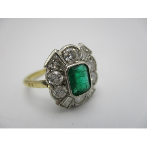 49 - An 18ct gold diamond and emerald cluster engagement ring, with central emerald cut emerald surrounde...