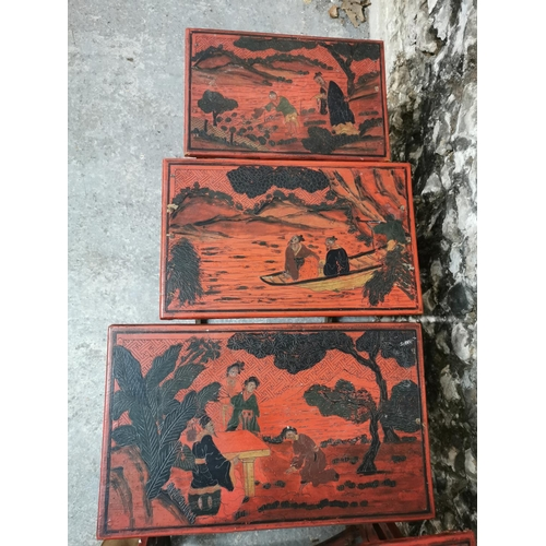 120 - A nest of four red lacquer Japanese side tables, the rectangular tops with figural scenes, supported...