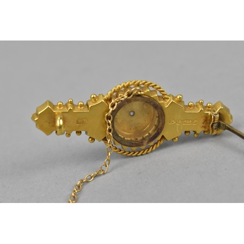 24 - A 15ct gold Edwardian Etruscan design mourning brooch, inset with seed pearls and a central old cut ...