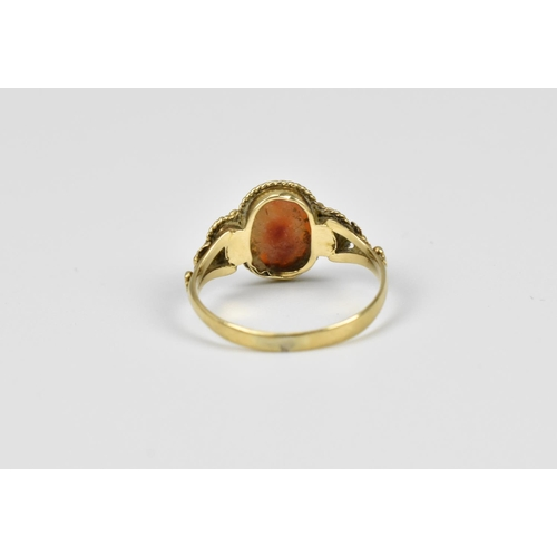 30 - A Georgian yellow metal carnelian cameo ring depicting a flower flanked with seed pearls, size I 1/2...