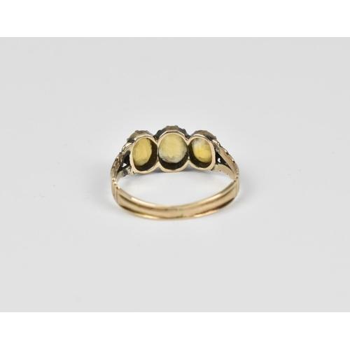 31 - A Georgian yellow metal dress ring set with three citrine stones, size L...
