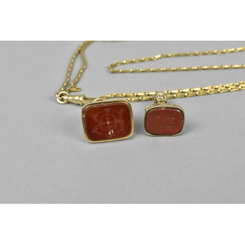 34 - A yellow metal elongated flat cable link fob chain, with two carnelian inset fobs etched with monogr...