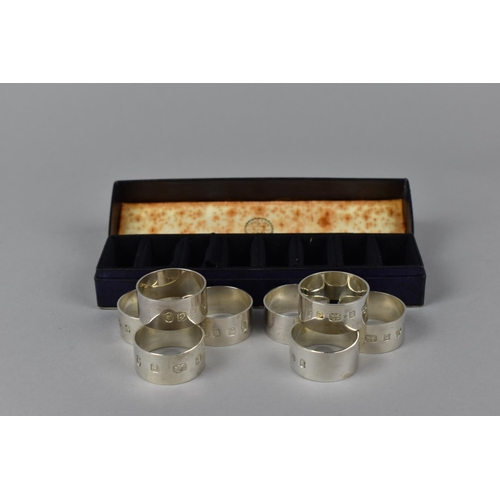 4 - A cased set of eight Elizabeth II silver napkin rings by Payne & Sons, Birmingham 1977, of plain des...