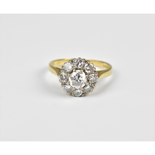 43 - An 18ct gold and diamond floral cluster ring, with central round cut diamond with a surround of eigh...