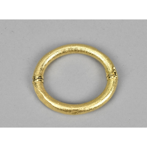 44 - An 18ct yellow gold bangle, of hollow round section with textured design and box clasp, inner diamet...