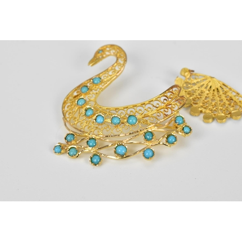 52 - A gold and turquoise brooch in the shape of a swan swimming, designed with filigree scrolls and turq...