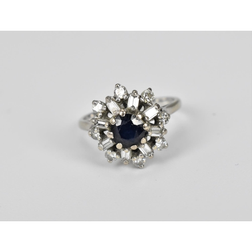 58 - A white gold, sapphire and diamond snowflake cluster ring, with central sapphire flanked with baguet...